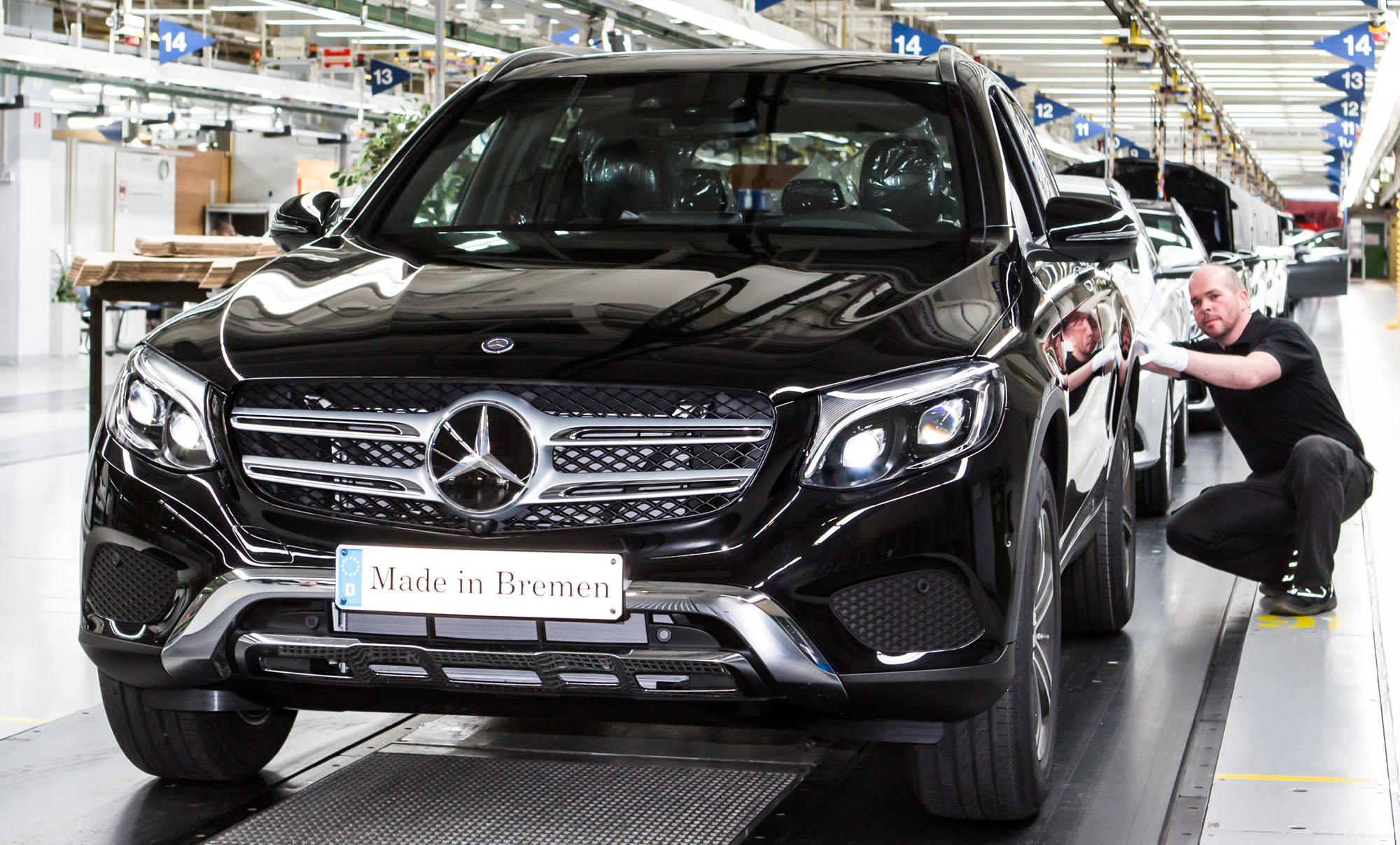 Ein Mann kniet neben einem neu produzierten dunklen Mercedes.
