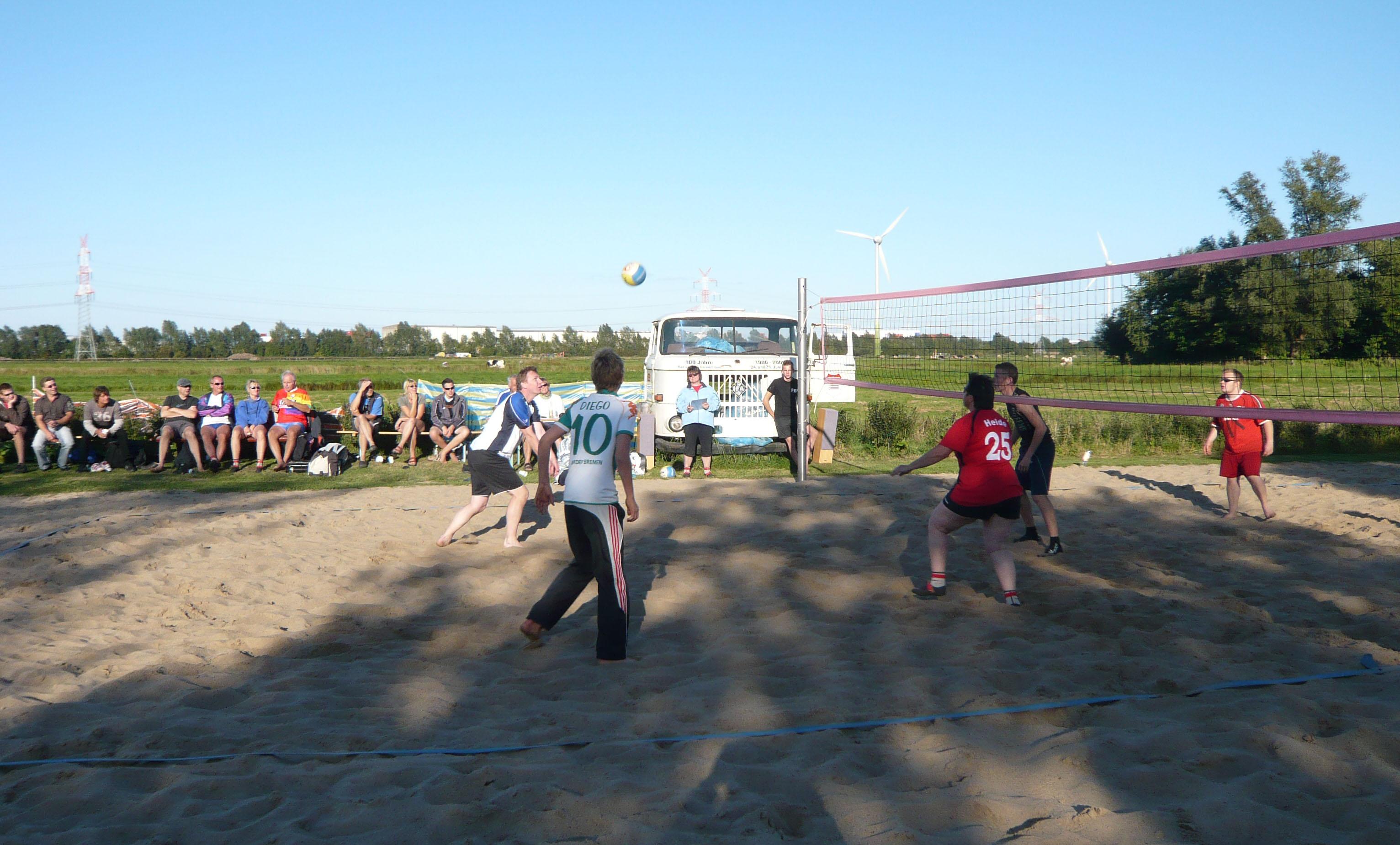 Eine Gruppe von leuten, die in Strom Beachvolleyball Spielen