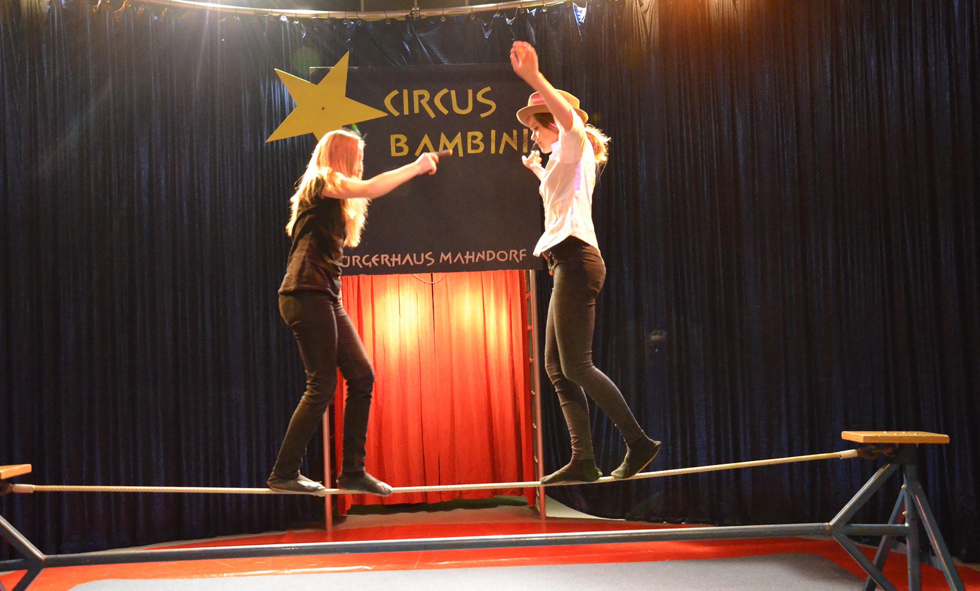 Zwei junge Artistinnen laufen in der Manege auf einem Seil aufeinander zu.