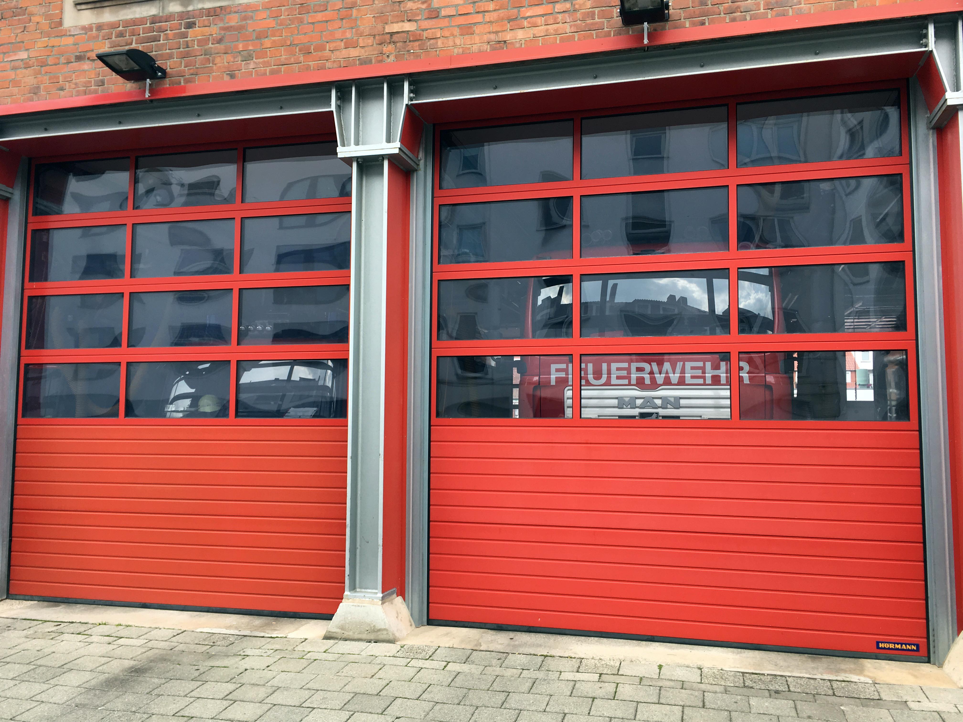 Feuerwehrautos, die hinter einem roten Feuerwehrtor stehen