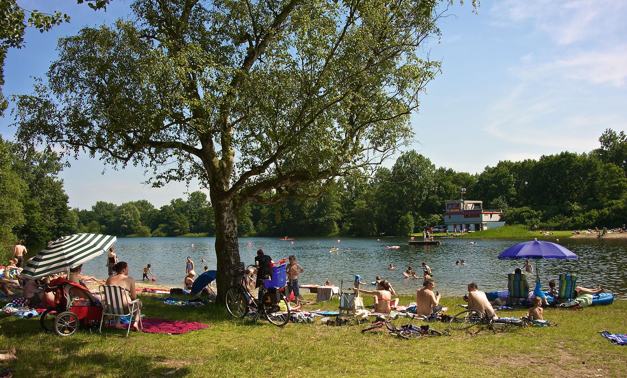 Menschen in Badebekleidung genießen den Sommer auf einer Wiese am Achterdieksee.