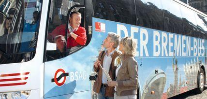Ein Mann und eine Frau reden mit dem im Bus sitzenden Fahrer des Bremen Busses.