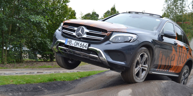 Ein Geländewagen auf der Teststrecke: Das rechte Vorderrad hängt in der Luft.