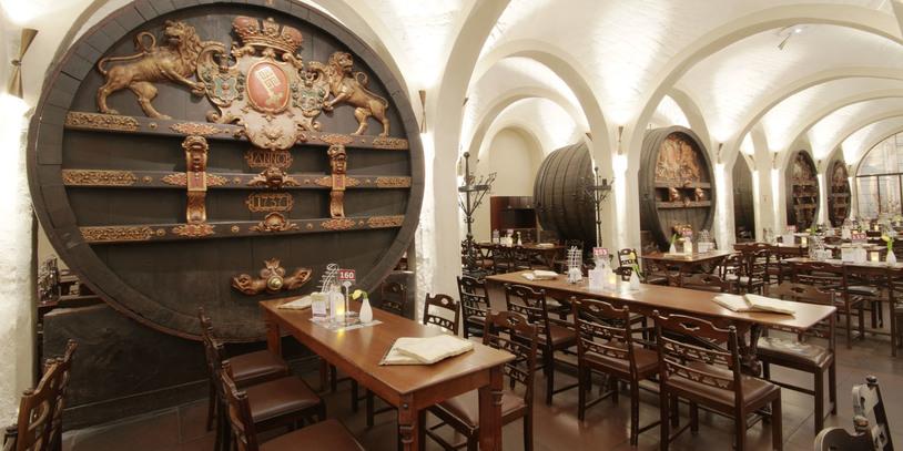 Der Ratskeller von innen, Tische und Stühle vor einem historischen Wappen, weiße Gewölbedecken.