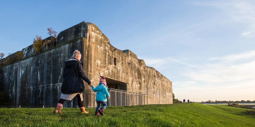 Ein großer Hochbunker, im Vordergrund eine Mutter mit ihrem Kind; Quelle: WFB/Jens Lemkühler
