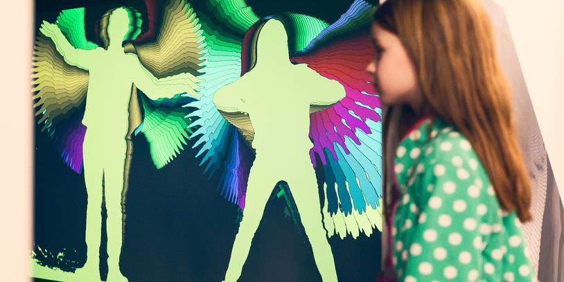 Ein Mädchen steht seitlich im Bild, im Hintergrund sind ihre Umrisse auf einer Leinwand mit vielen verschiedenen Farben umrandet.