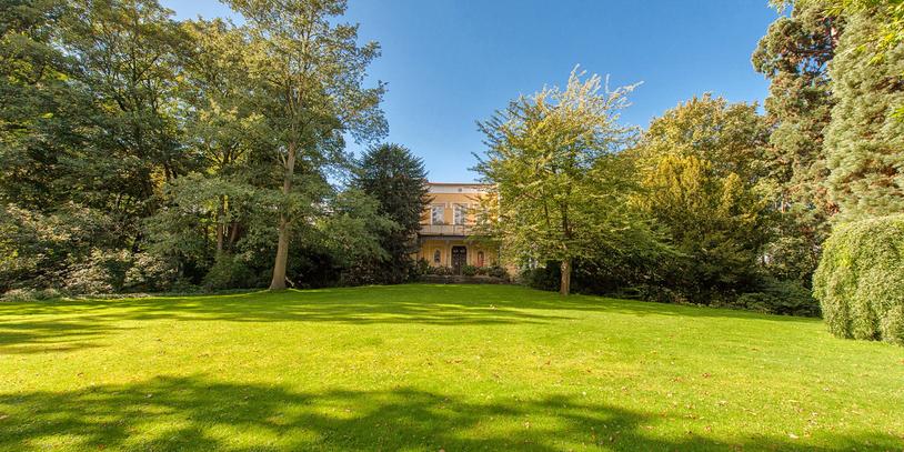 Eine große Grünfläche vor einem gelben Haus, das ganz im Hintergrund liegt, das Schloss in Sebaldsbrück