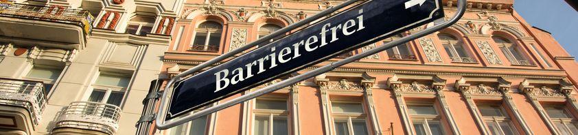 Auf einem blauen Schild steht mit weißer Schrift das Wort Barrierefrei.