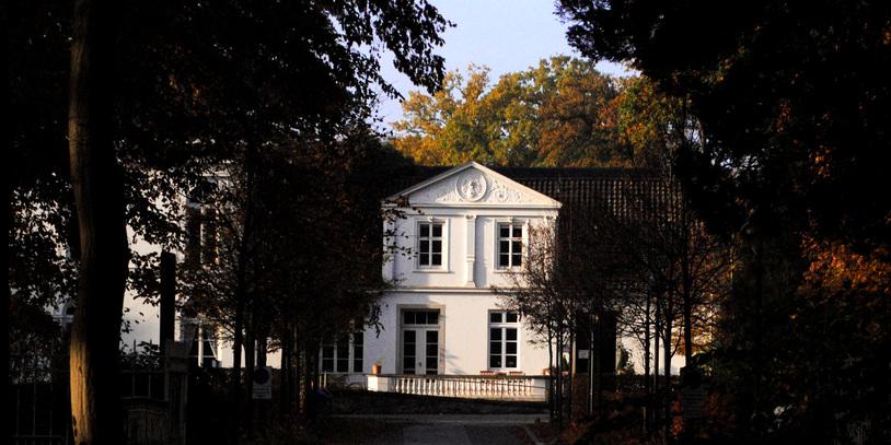 Eine herrschaftliche Villa in einer Parkanlage.