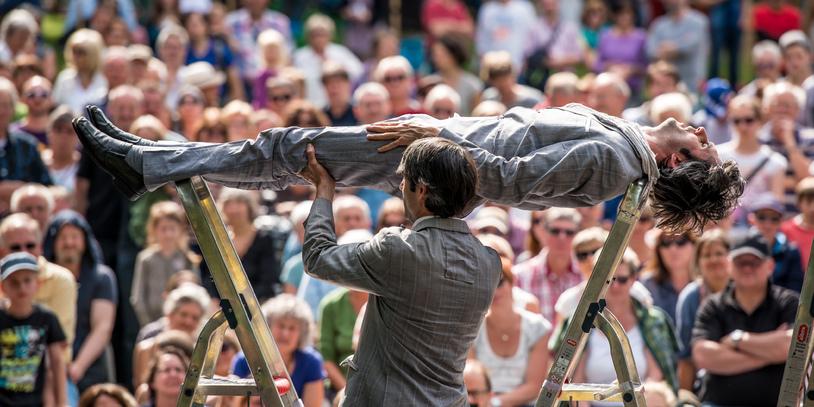 Zwei Akrobaten mit Leitern vor Publikum
