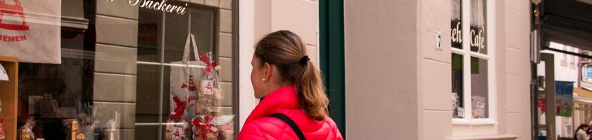 Ein Frau blickt auf die Auslage in einem Schaufenster.