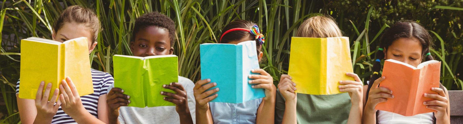 Kinder lesen Bücher im Park.
