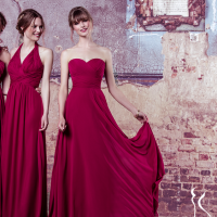 Drei Models stehen in roten Kleidern vor einer Wand.