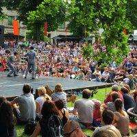 Zahlreiche Menschen vor einer Bühne im Freien mit Kleinkünstlern.