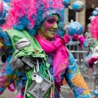 Eine mit Weltkugeln und bunten Farben geschmückte Frau zelebriert den Samba Karneval