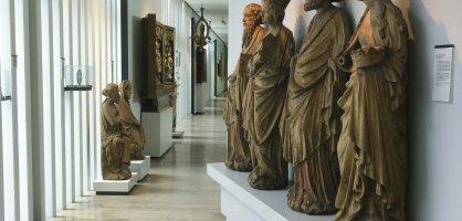 Vier große Steinfiguren, die auf einem weißen Sockel in einem Flur stehen.