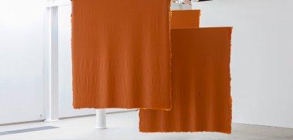 Orange, hängende Vierecke in einem weißen Raum.