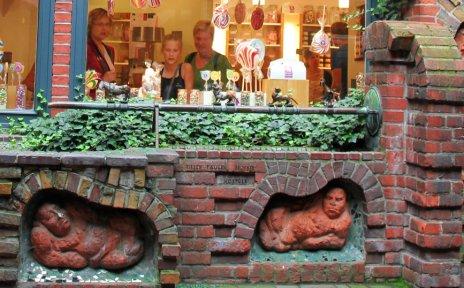 Roter Backsteinbrunnen mit sieben steinernen, in die Wand eingelassenen Figuren drumherum.