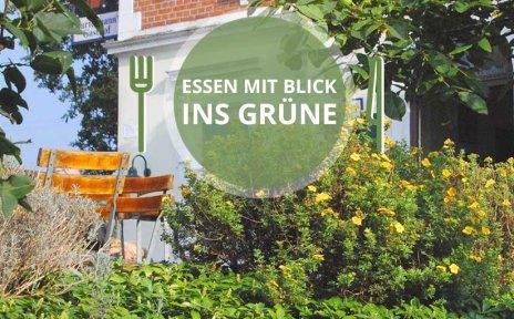 """Ein im grünen liegendes Gasthaus im Hintergrund, im Vordergrund die Aufschrift """"Essen im Grünen""""."""