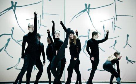 Tänzer auf der Bühne in engen schwarzen Anzügen.