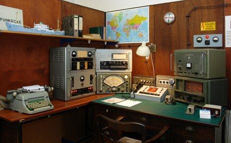 Ein Schreibtisch mit älteren Rundfunkgeräten.