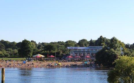 Blick auf Café Sand an einem sommerlichen Tag mit vielen Menschen am Strand.