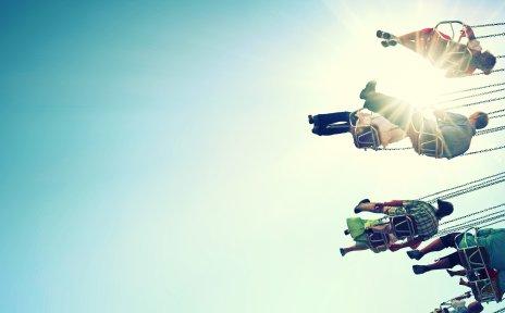 Gondeln eines Kettenkarussells vor blauem Himmel