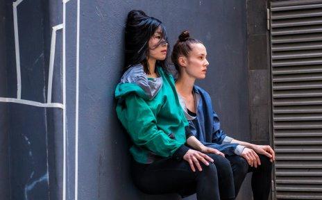 Zwei Künstlerinnen sitzen an einer Wand