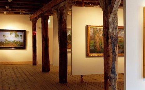 Ein Ausstellungssaal mit Gemälden, Dielenboden und Holzbalken.