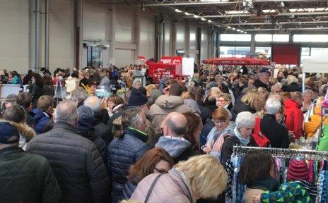 Eine Aufnahme vom Markttreiben: Viele Leute sind in der Markthalle und gucken sich die Stände an.