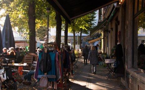 Kleidung hängt an einer Stange vor einem Geschäft, Menschen sitzen in einem Café in der Sonne