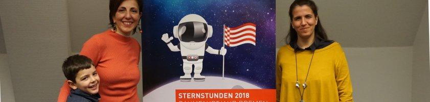 Die beiden Koordinatorinnen der WIA-Bremen posieren mit einem Jungen vor einem STERNSTUNDEN2018 Roll Up.