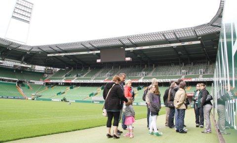 Im Werderstadion stehen Leute während einer Stadionführung am Spielfeldrand.