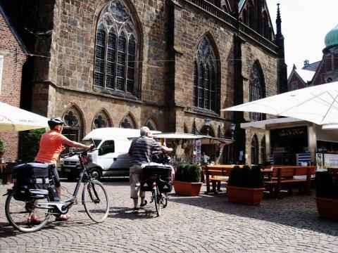 Zwei Radfahrer schieben ihr Rad durch die Bremer Innenstadt