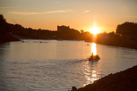 Die Sonne senkt sich über der Weser und taucht die Landschaft in goldenes Licht.