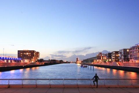Ein Mann steht am Kopf des Hafenbeckens Europahafen und blickt auf den Sonnenuntergang