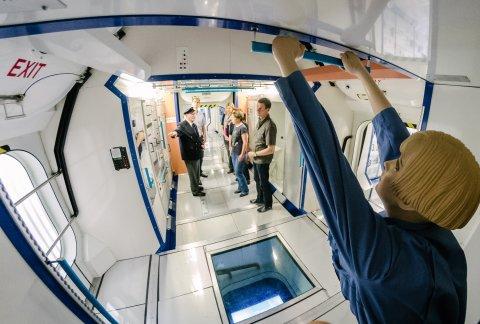 Einer Besuchergruppe wird im Modell des Columbus-Moduls bei Airbus Bremen Wissenswertes über das Leben im All vermittelt