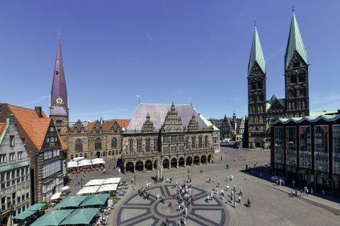 Vogelperspektive auf einen Platz, über dem Menschen laufen. Die Aufnahme zeigt mehrere Gebäude sowie den Dom mit zwei Türmen.