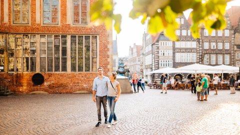 Eine Frau und ein Mann laufen am Bremer Rathaus vorbei. Im Hintergrund sieht man mehrere Menschen bei den Bremer Stadtmusikanten stehen.