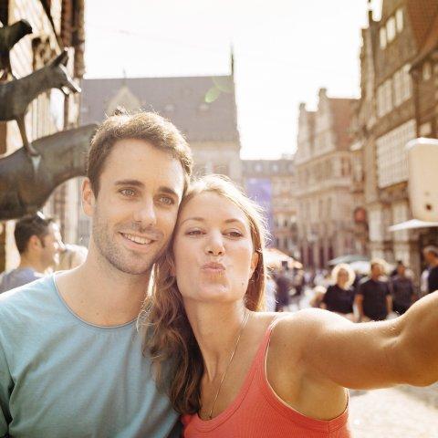 Ein Pärchen macht ein Selfie vor den Bremer Stadtmusikanten.