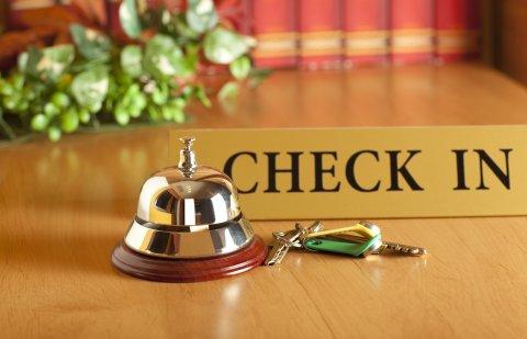 Eine Klingel, ein Schlüssel und ein Schild mit der Aufschrift Check-In