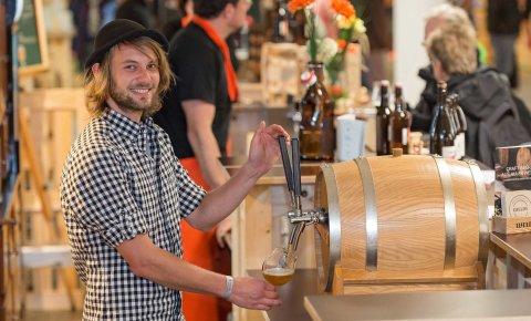 Ein junger Mann zapft Bier beim Craft Beer Event in der Messe Bremen.