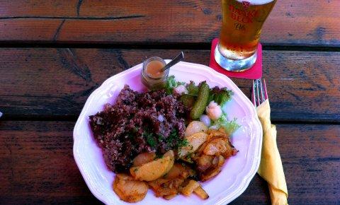 Ein Teller mit Knipp, Bratkartoffeln, Salat, saurer Gurke und Apfelmuß