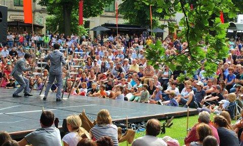 Viele Menschen schauen Künstlern auf einer Bühne bei La Strada zu.