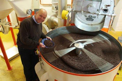 Eine Person steht mit Hingabe an einer Röstmaschine und geht seiner Arbeit mit den Kaffeebohnen nach