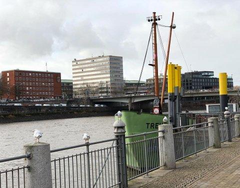 Ein Blick vom Weserufer auf die Weser. Vorne rechts im Bild liegt das grüne Schiff MS Treue, auf dem regelmäßig Veranstaltungen und Partys stattfinden.