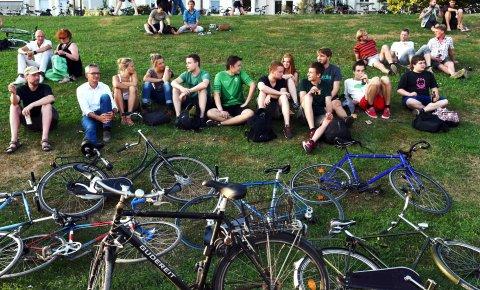 Menschen sitzen am Osterdeich, vor ihnen ihre Fahrräder im Gras.