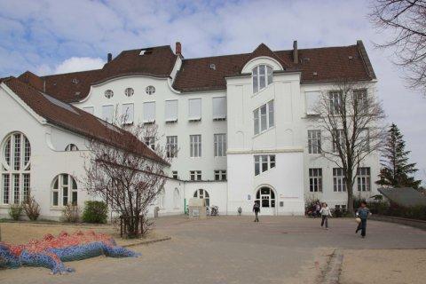 Weißes Gebäude des Schulmuseums mit Kindern davor.