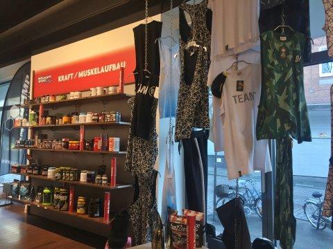 Sportklamotten hängen an der Wand und verschiedene Sportlernahrung steht im Regal.