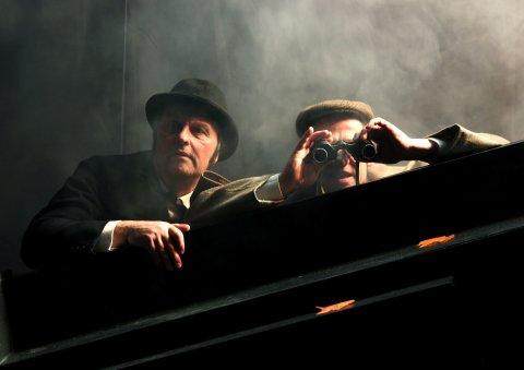 Zwei Schauspieler suchen auf der Bühne jemanden mit einem Fernglas.